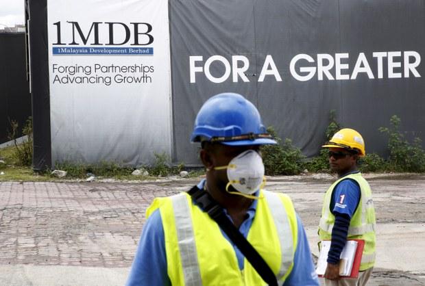 Pekerja binaan berdiri di hadapan papan iklan 1Malaysia Development Berhad (1MDB) di tapak projek pembangunan Tun Razak Exchange di Kuala Lumpur, Malaysia 3 Februari 2016.