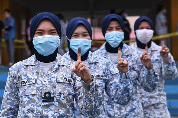 Anggota Tentera Laut Diraja Malaysia menunjukkan jari yang telah dicelup dengan warna ungu menandakan telah membuang undi awal sempena Pilihan Raya Negeri (PRN) Ke-16 Sabah di Sekolah Kebangsaan Pangkalan TLDM, Sepanggar, Sabah,  22 September, 2020..